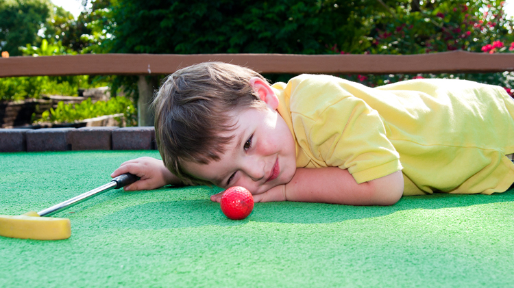 Child playing mini golf